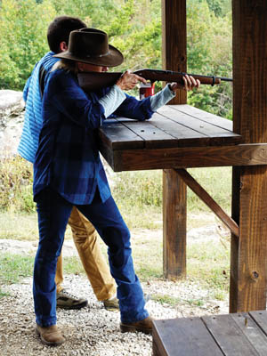 Joyce Wagoner shooting a rifle, assisted by Morgan.